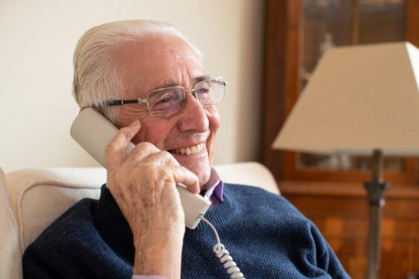 older man using home phone 600px